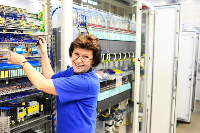Production and assembly of microelectronics in a hi-tech factory. Older woman assembles components -smiling portrait royalty free stock photos