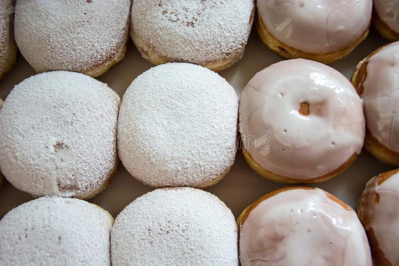 Production of donuts with icing and powdered sugar on a counter. Closeup stock image