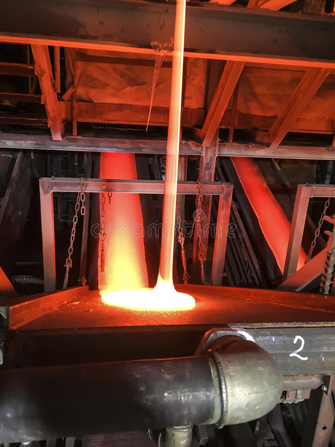 Production of enamel, the streams of molten glass. At the installation royalty free stock images