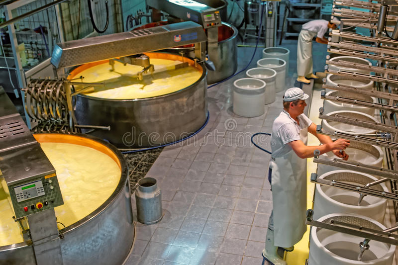 Production of Gruyere cheese at the cheese factory in a historic. GRUYERE, SWITZERLAND - JANUARY 2, 2015: Production of Gruyere cheese at the cheese factory in a stock photos