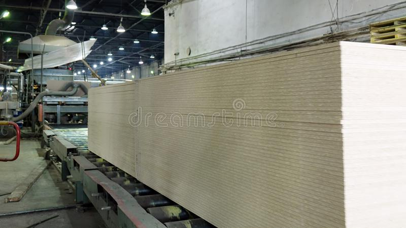 Production of laminated fiberboard. Fibreboard sheets for furniture production royalty free stock photo