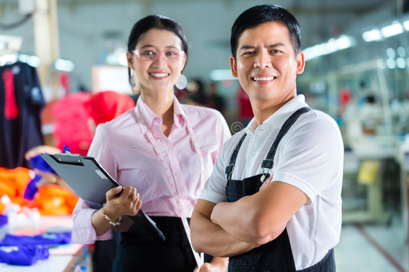 Production manager and designer in Asian factory stock photography