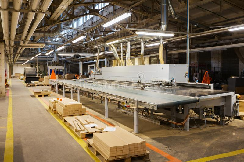Chipboards on conveyer at furniture factory. Production, manufacture and woodworking industry concept - chipboards processing on conveyer at furniture factory royalty free stock photos