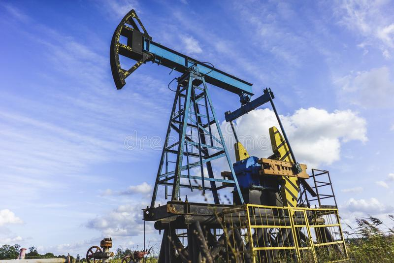 Production of Oil: Oil Rig on Blue Sky Background. Oil Drilling Rig, Extraction of Oil, Pump Jack and Oil Wellhead, Industry Equipment Close Up, Oilfield, Oil stock images