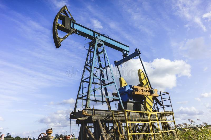 Production of Oil: Oil Rig on Blue Sky Background. Oil Drilling Rig, Extraction of Oil, Pump Jack and Oil Wellhead, Industry Equipment Close Up, Oilfield, Oil royalty free stock photo