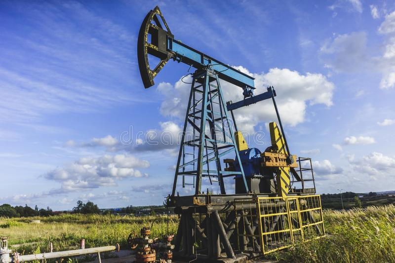 Production of Oil: Oil Rig on Blue Sky Background. Oil Drilling Rig, Extraction of Oil, Pump Jack and Oil Wellhead, Industry Equipment Close Up, Oilfield, Oil stock photos