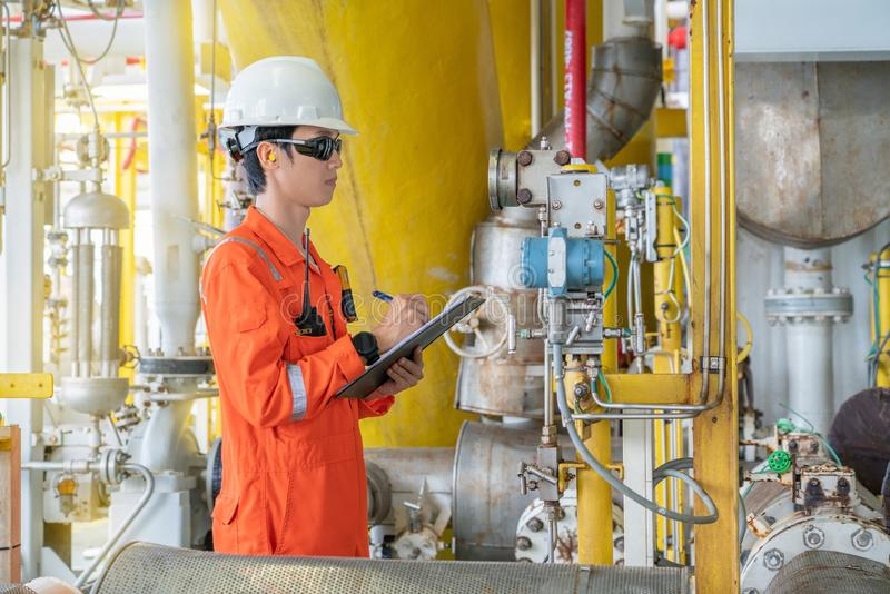 Production operator on oil and gas central processing platform while log reading of differential pressure gauge. royalty free stock photos