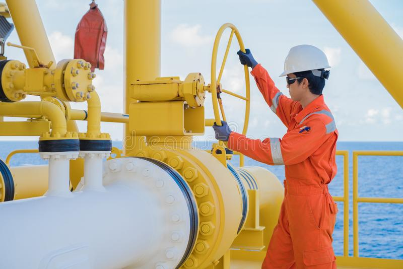Production operator opening ball valve at offshore oil and gas wellhead remote platform. royalty free stock photos