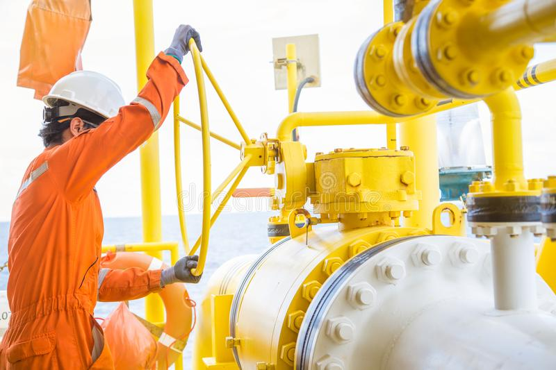 Production operator opening big ball valve to allow gas flow through pipeline at offshore oil and gas platform. royalty free stock images