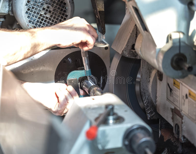 Production of parts on a metal lathe. A worker checks the size w royalty free stock photo