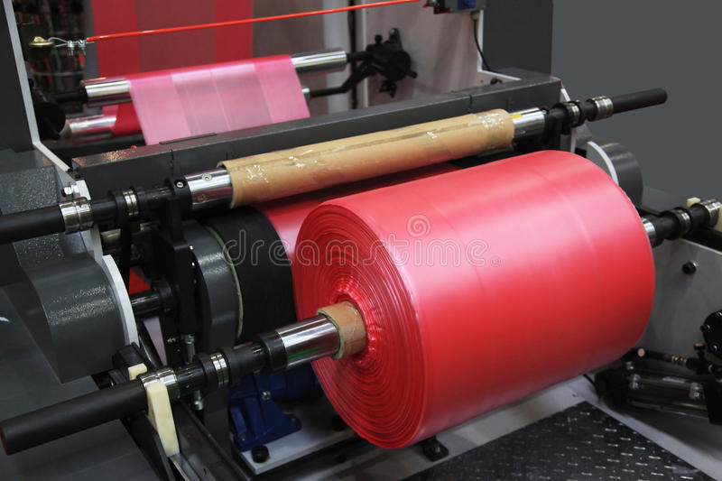 Production of plastic bags. Extruder of polyethylene for process production of plastic bags stock photo