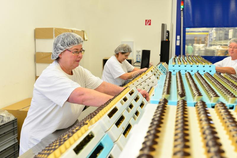 Production of pralines in a factory for the food industry - women working on the assembly line. Production of pralines in a factory for the food industry stock photo