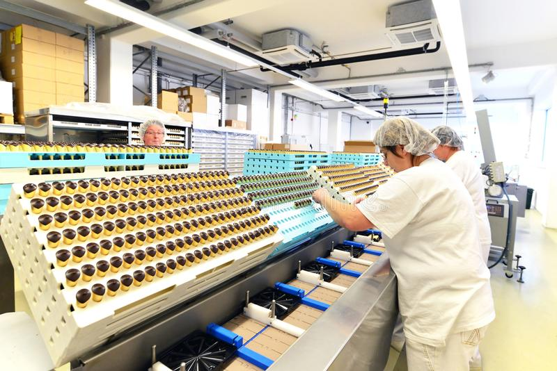 Production of pralines in a factory for the food industry - women working on the assembly line. Production of pralines in a factory for the food industry royalty free stock photo