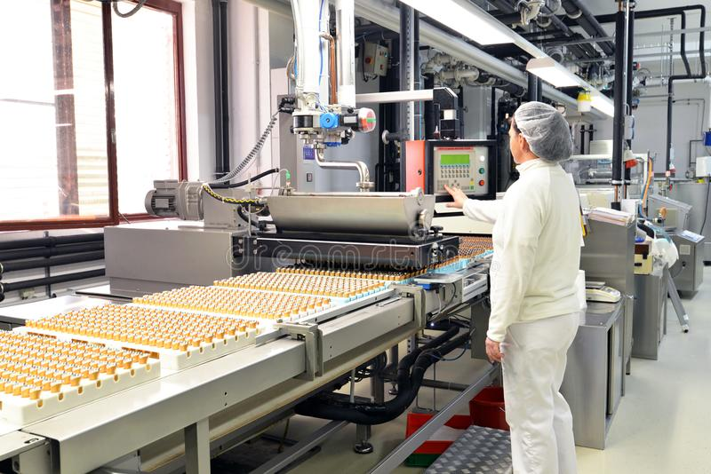 Production of pralines in a factory for the food industry - conveyor belt worker with chocolate stock photo