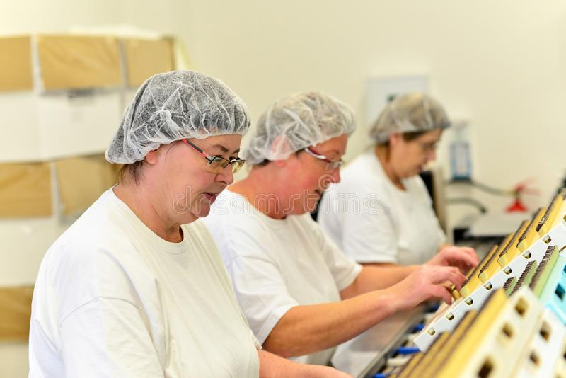 Production of pralines in a factory for the food industry. Group female workers stock photos