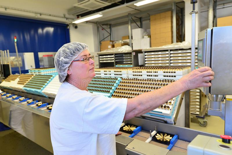 Production of pralines in a factory for the food industry - women working on the assembly line. Production of pralines in a factory for the food industry - woman royalty free stock photos