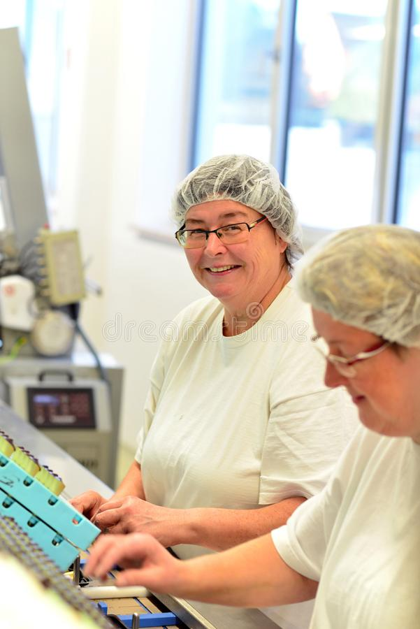 Production of pralines in a factory for the food industry - women working on the assembly line royalty free stock photo
