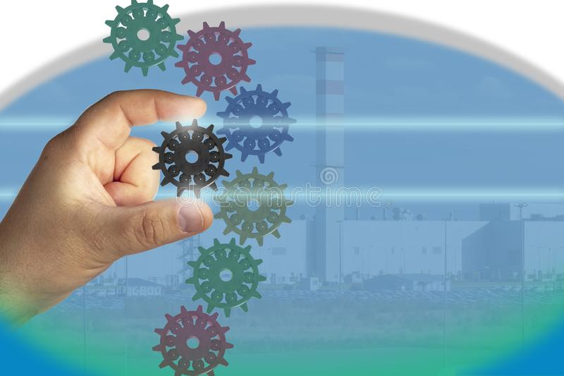 Production processes. Adjustment, optimization, improvement, control. Production processes. The hand holds one gear from the common mechanism. Adjustment stock images