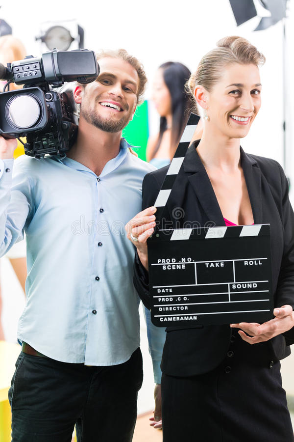 Production team with camera and take clap on film set or studio. Team or Cameraman with camera and women with take clap or board on Film Set royalty free stock images