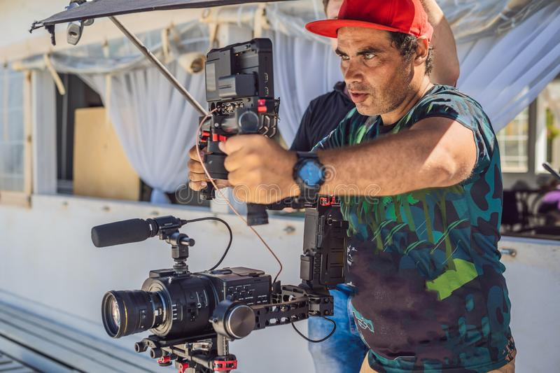 The production team on a commercial video shoot. Steadicam operator uses the 3-axis camera stabilizer and cinema-grade. Camera royalty free stock photos