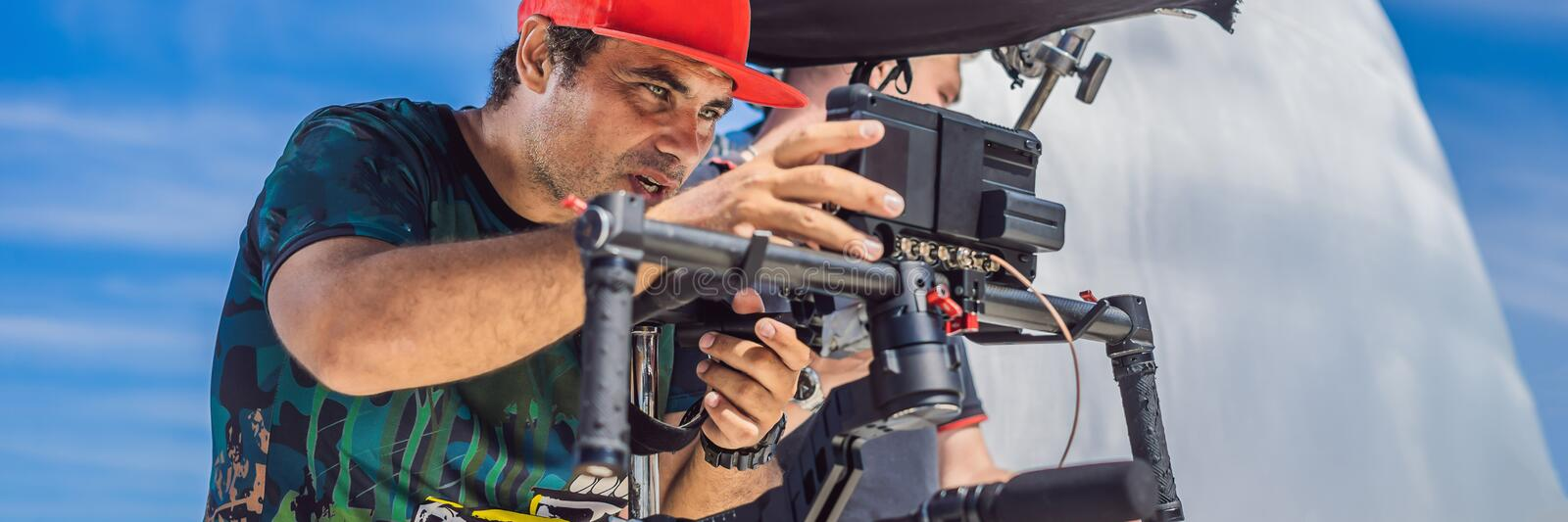 The production team on a commercial video shoot. Steadicam operator uses the 3-axis camera stabilizer and cinema-grade. Camera. BANNER, LONG FORMAT royalty free stock photography