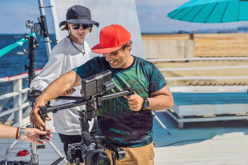 The production team on a commercial video shoot. Steadicam operator uses the 3-axis camera stabilizer and cinema-grade. Camera royalty free stock photography