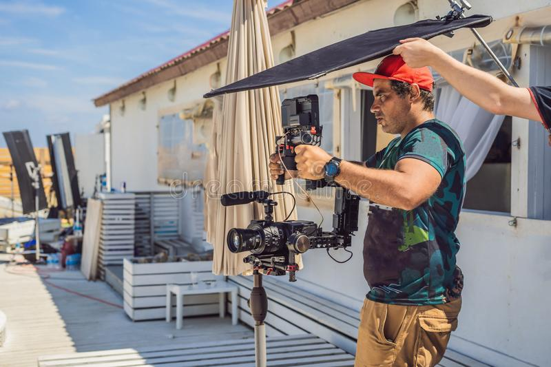 The production team on a commercial video shoot. Steadicam operator uses the 3-axis camera stabilizer and cinema-grade. Camera stock photography