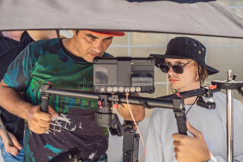 The production team on a commercial video shoot. Steadicam operator uses the 3-axis camera stabilizer and cinema-grade. Camera royalty free stock image