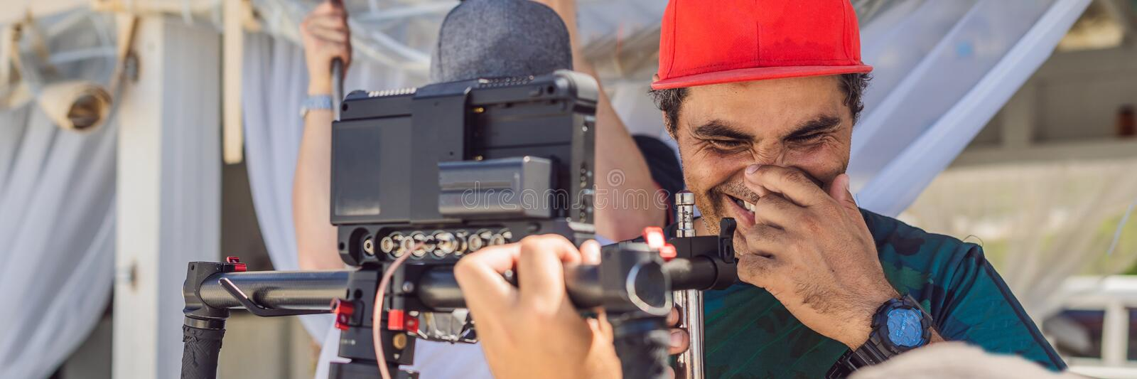 The production team on a commercial video shoot. Steadicam operator uses the 3-axis camera stabilizer and cinema-grade. Camera. BANNER, LONG FORMAT stock photography