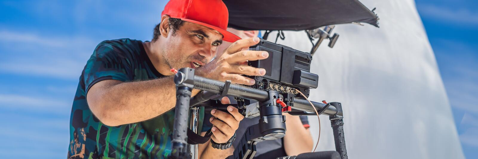 The production team on a commercial video shoot. Steadicam operator uses the 3-axis camera stabilizer and cinema-grade. Camera. BANNER, LONG FORMAT royalty free stock photo