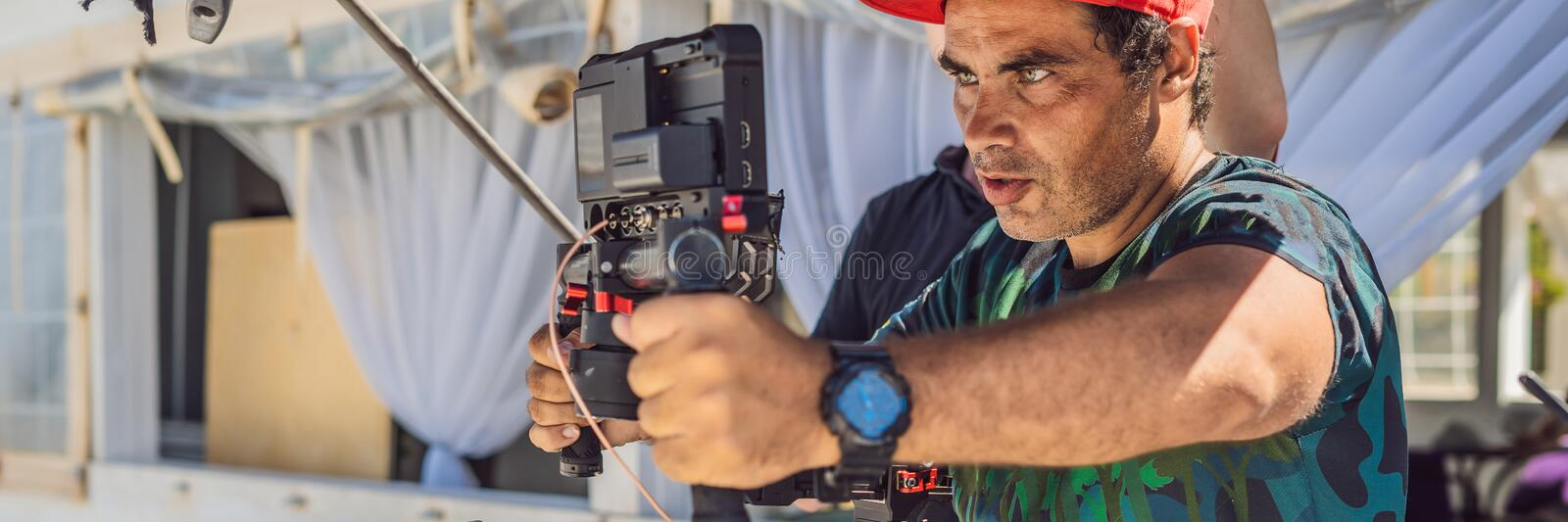 The production team on a commercial video shoot. Steadicam operator uses the 3-axis camera stabilizer and cinema-grade. Camera. BANNER, LONG FORMAT stock images