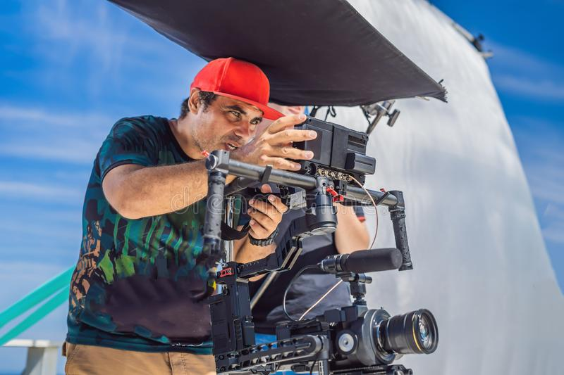 The production team on a commercial video shoot. Steadicam operator uses the 3-axis camera stabilizer and cinema-grade. Camera stock images