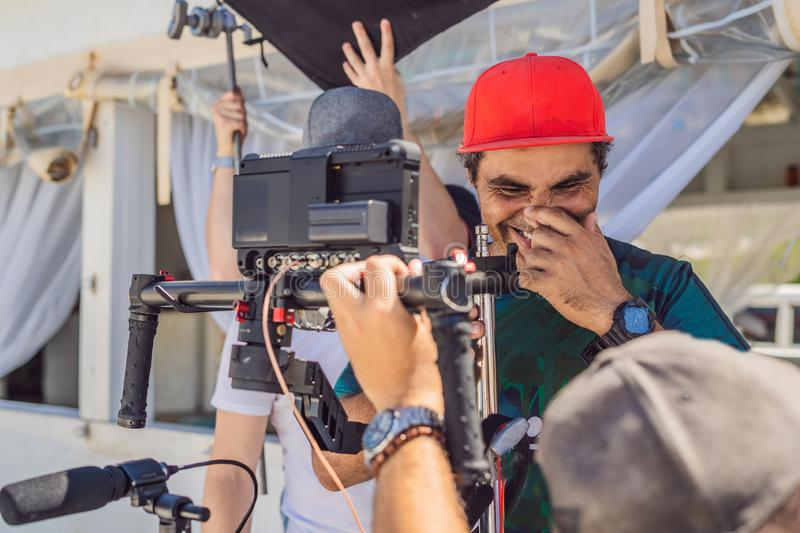 The production team on a commercial video shoot. Steadicam operator uses the 3-axis camera stabilizer and cinema-grade. Camera royalty free stock photo