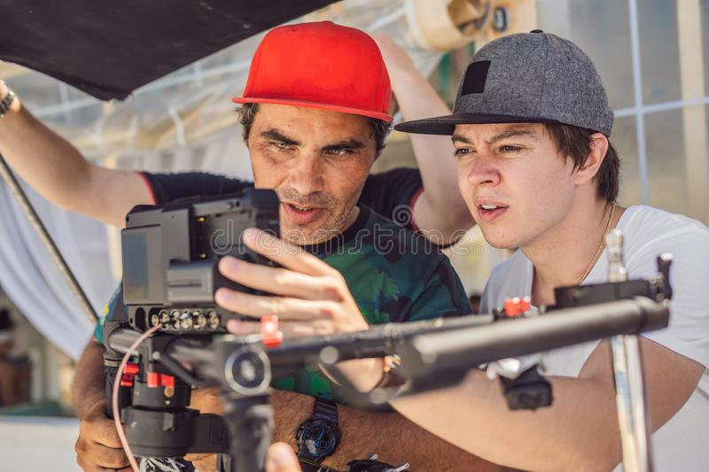 The production team on a commercial video shoot. Steadicam operator uses the 3-axis camera stabilizer and cinema-grade. Camera stock photos