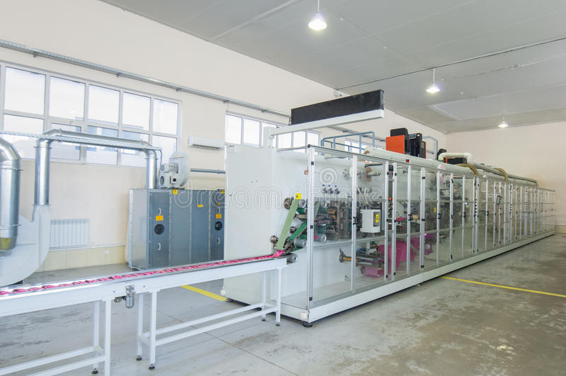 Production of women`s sanitary napkins. Factory and equipment for the production of female sanitary napkins royalty free stock photography