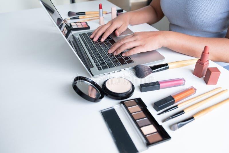 Producto cosmético del blogger de la mujer actual que se sienta en tableta delantera y la difusión a la red social por Internet,  imagenes de archivo