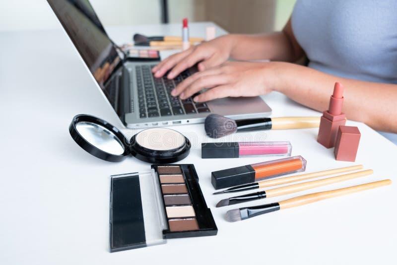 Producto cosmético del blogger de la mujer actual que se sienta en tableta delantera y la difusión a la red social por Internet,  imagen de archivo