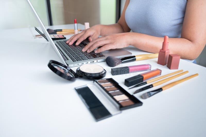 Producto cosmético del blogger de la mujer actual que se sienta en tableta delantera y la difusión a la red social por Internet,  foto de archivo