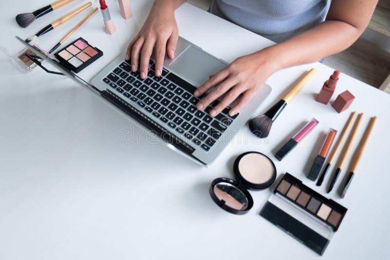 Producto cosmético del blogger de la mujer actual que se sienta en tableta delantera y la difusión a la red social por Internet,  fotos de archivo libres de regalías