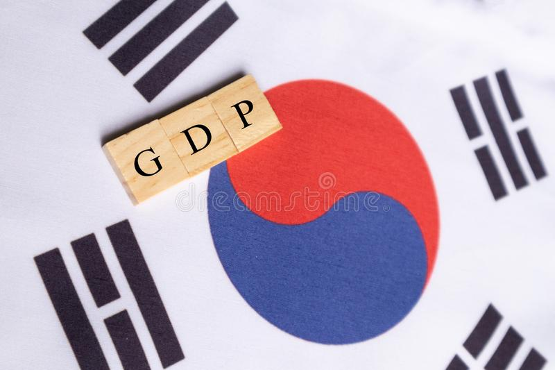 Producto interno bruto o GDP de la Corea del Sur en letras de molde de madera en bandera surcoreana foto de archivo