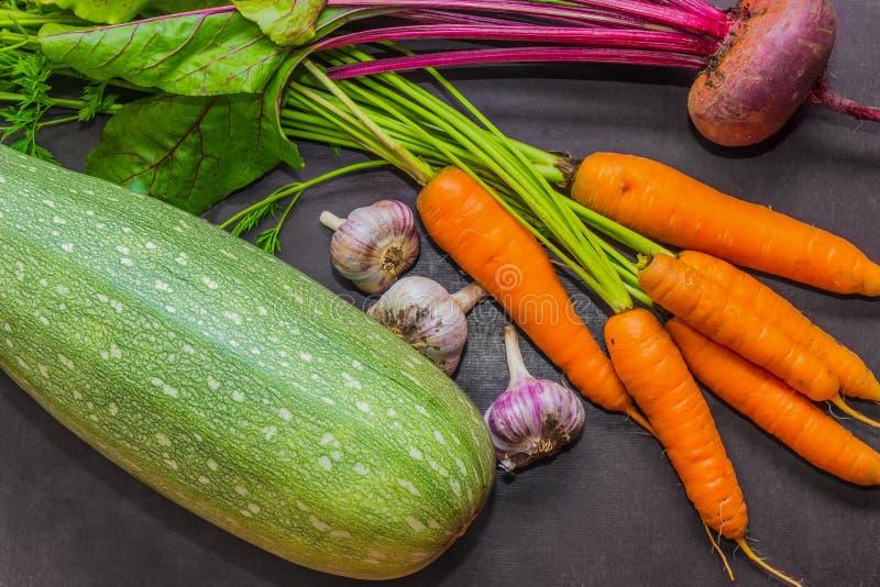 Producto-vehículos frescos de vegetables Calabacín, zanahorias, ajo y remolachas en la tabla cosecha imagen de archivo libre de regalías