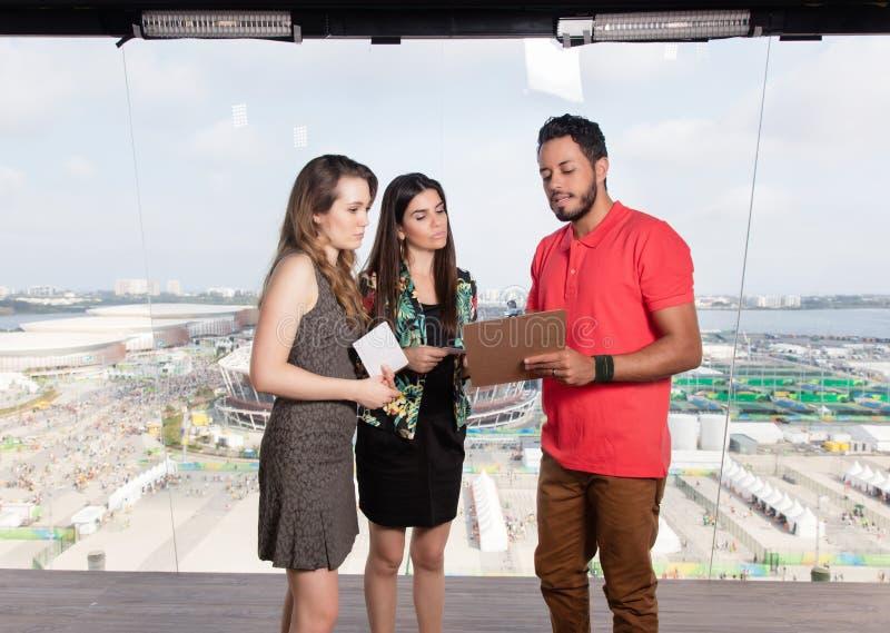 Productor de televisión y presentadores femeninos en el estudio de la TV fotos de archivo libres de regalías