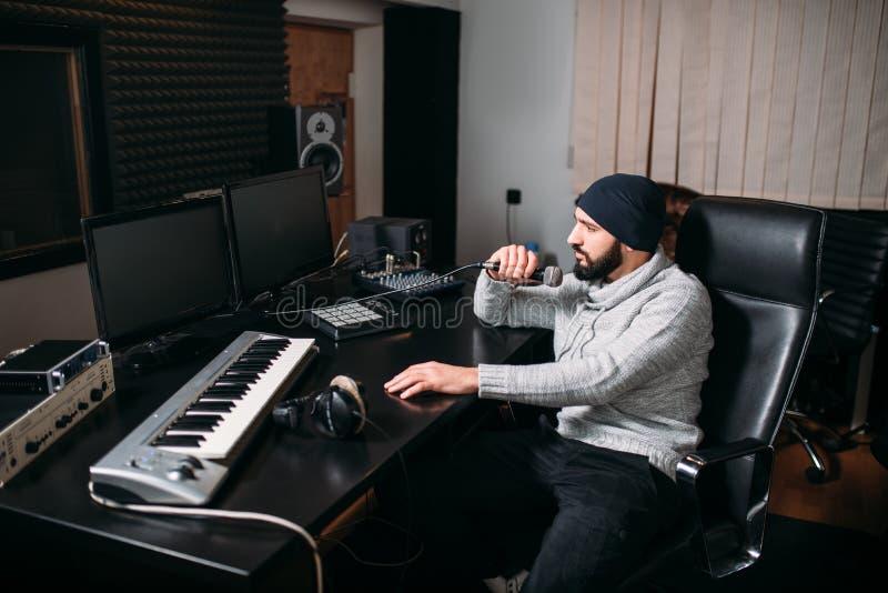 Productor sano con el micrófono en estudio de la música imagen de archivo