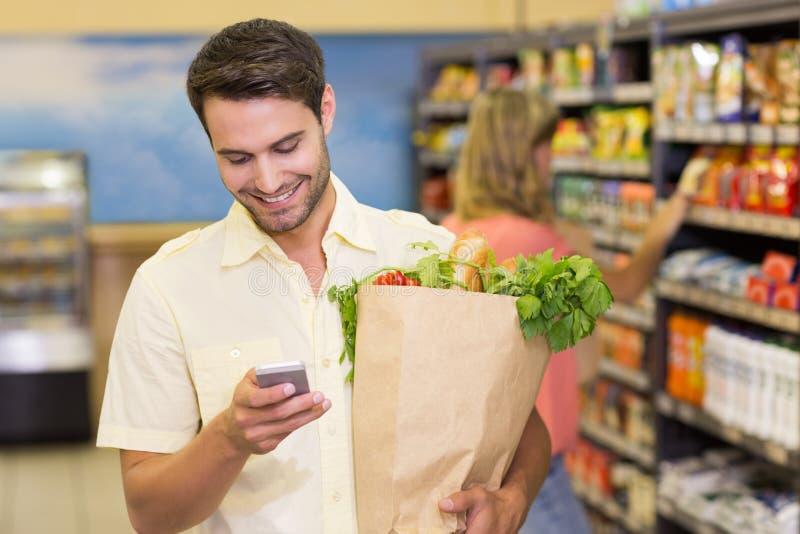 Productos alimenticios y usar de compra sonrientes del hombre hermoso su smartphone imagen de archivo libre de regalías