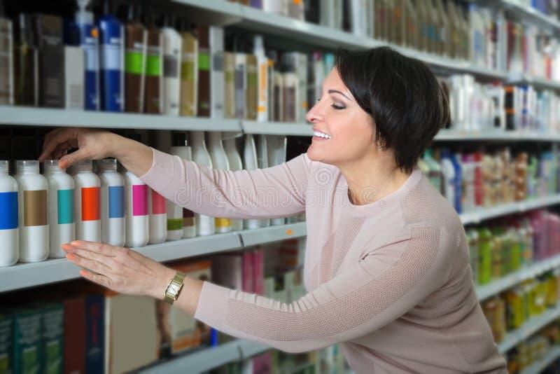 Productos de compra del cuidado del cabello de la mujer elegante fotografía de archivo libre de regalías