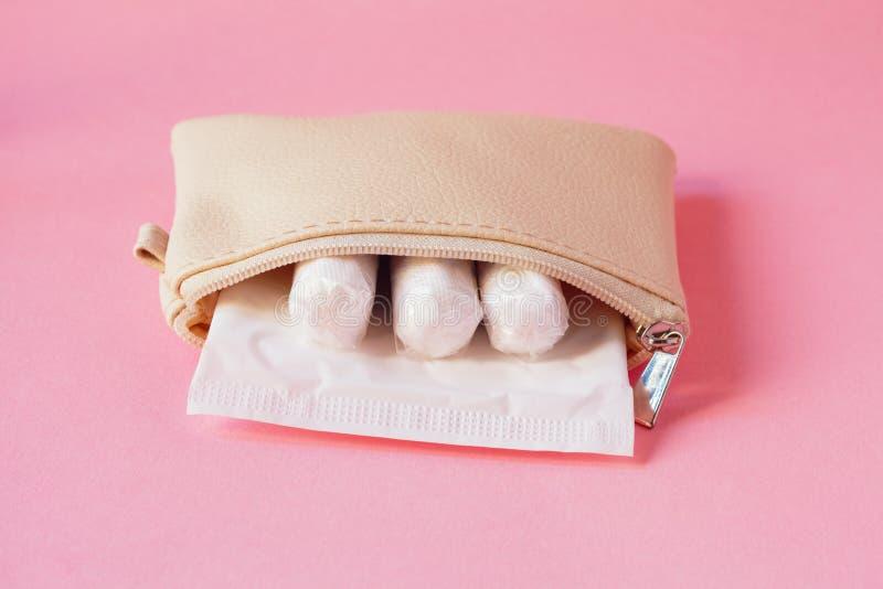 productos de higiene íntimos - cojín sanitario y tapones en el bolso blanco en fondo rosado foto de archivo libre de regalías