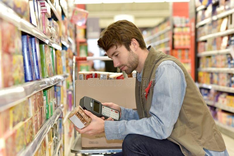 Productos de la exploración del vendedor en supermercado foto de archivo