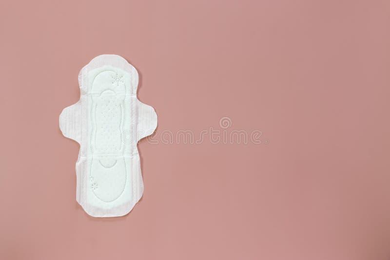 Productos de la higiene de las mujeres o cojín sanitario en fondo rosado foto de archivo