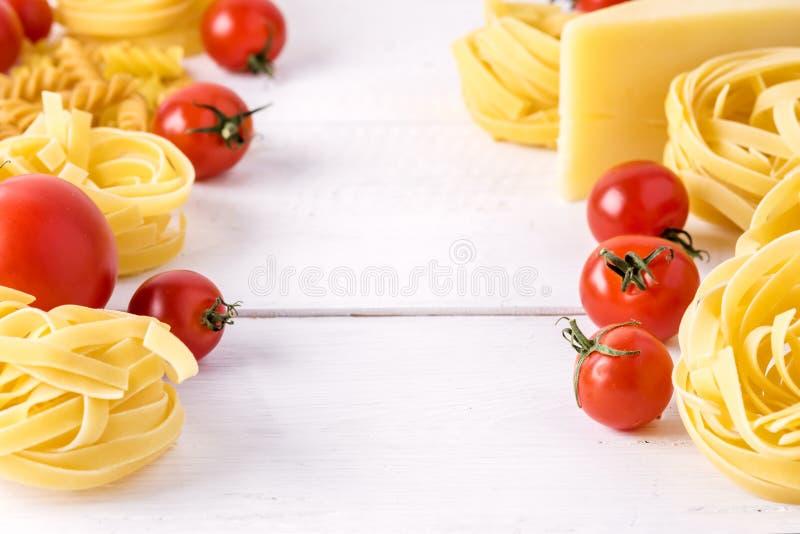 Productos de las pastas con el cierre blanco del fondo de las pastas del queso del tomate de Fusili del Fettuccine de la comida i imagenes de archivo