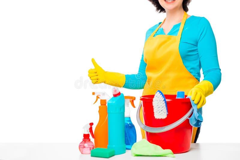 Productos de limpieza en una tabla blanca y un ama de casa feliz imagen de archivo libre de regalías